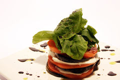 Stacked rocket tomato and mozarella salad. With dressing on the side Stock Image