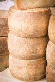 Stacked rounded cheese for sale in market Royalty Free Stock Photography
