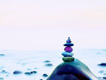 Stacked rounded stones at sea. Polished pebbles on dark wet rock,  smooth water Stock Images