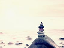 Stacked rounded stones at sea. Polished pebbles on dark wet rock,  smooth water Stock Photos