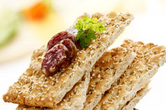 Stacked sesame crispbread with slices of salami Stock Photography