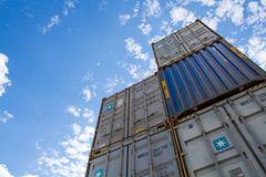 Stacked Shipping Containers. Looking up from ground level at cargo and shipping containers stacked on top of each other with blue sky above and copy space stock photos