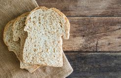 Stacked slice whole wheat sandwich bread on gunny sack cloth on wood table royalty free stock photos