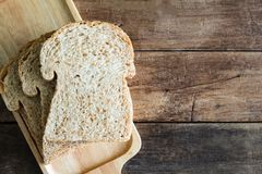 Stacked slice whole wheat sandwich bread on wooden plate on wood table royalty free stock photo