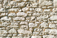 Stacked stone wall background horizontal. Sunlit ancient natural stone wall Stock Photos