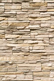 Stacked stone wall background vertical. Stacked stone wall background of warm brown tones in vertical format Royalty Free Stock Photo
