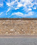 Stacked stone wall with skies and gravel road horizontal seamless pattern Royalty Free Stock Images