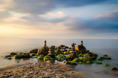 Stacked stones in the Baltic Sea. Some people stacked stones right in front of the beach in north Germany. together with the clouds this long exposure in nice stock image