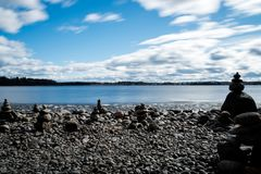 Zen stones on lakeshore. Stacked stones on a beach at lake Pyhäjärvi on an early spring day in Tampere, Finland. Long exposure Royalty Free Stock Image