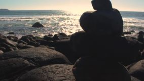 Stacked stones on the beach. Tilt up video. Florianpolis, Santa Catarina, Brazil. Beautiful sunrise on the beach in a bright day. Relaxing with friends stock video