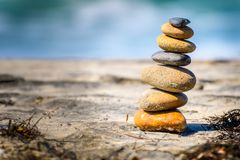 Stacked stones naturally balanced on sand. Stacked stones naturally balanced on a sunny day by the beach. Rock Balancing stock photography