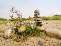 Stacked stones in pyramid on the grass. Coastline in summer Royalty Free Stock Photos