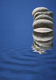 Stacked Stones Refelcting in Blue Water Stock Photography
