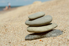 Stacked stones at the sand Stock Images