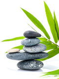 The stacked of Stones spa treatment scene and bamboo leaves . The stacked of Stones spa treatment scene and bamboo leaves with raindrop zen like concepts Royalty Free Stock Photos