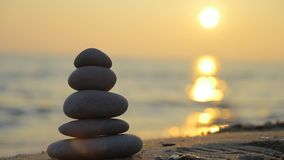 Stacked stones and sunset stock video footage