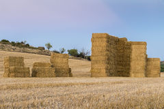 Stacked straw bales on a harvested field. Groups of stacked straw bales on a harvested cereal field Stock Image