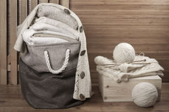 Stacked sweaters in fabric basket Royalty Free Stock Photos