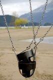 Stacked swing seats on chains near Harrison lake Royalty Free Stock Image