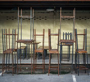 Stacked tables and chairs in front of closed store. Old tables and chairs in front of closed store Royalty Free Stock Images