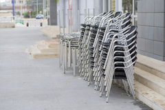 Stacked tables and chairs. Tables and chairs terrace bar, stacked on the street Stock Photography