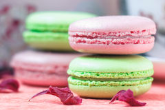 Stacked, tasty pink and green Macaroons, colorful delicious French pastries, strawberry and pistachio macaroons. Decorated with dry peony petals on pink paper Royalty Free Stock Images