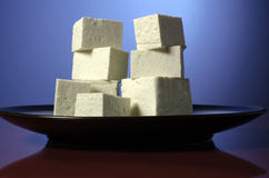 Stacked tofu cubes on a plate. Cubes of Tofu stacked on a plate with a colorful background Stock Photos