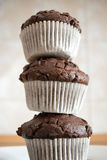 Stacked tower from hommade chocolate cupcakes. Three chocolate cupcakes stacked to form a tower in the kitchen Stock Image