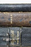 Close Up Three Stacked Leather Antique Bibles with Antique Metal. Stacked trio of antique Bibles with small antique cross made of wood metal and nails in Stock Photo