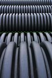 Black plastic curvilinear PVC pipe. Stacked tubes of corrugated polyethylene align in the distance.  Hollow and set for drainage during construction, the ridges Royalty Free Stock Photo