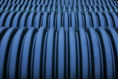 Black plastic curvilinear PVC pipe. Stacked tubes of corrugated polyethylene align in the distance.  Hollow and set for drainage during construction, the ridges Stock Image