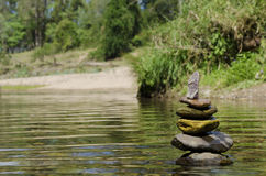 Stacked up balanced rocks in river Royalty Free Stock Images