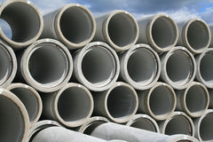 Stacked up water pipes. A series of water pipes made of concrete stacked up. Background of sky and foreground of more water pipes Stock Images