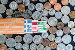 Stacked US Coins surrounded by coins and paper rolls. On table Royalty Free Stock Photography