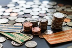 Stacked US Coins surrounded by coins and paper rolls. On table Stock Image