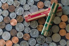 Stacked US Coins surrounded by coins and paper rolls. On table Royalty Free Stock Photos