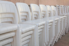 Stacked white chairs. Plastic chairs stacked up during winter off season Stock Photos