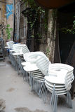 stacked white chairs in a backyard Stock Photos