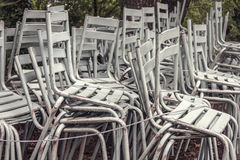 Stacked white chairs outdoors. A pile of stacked white and old chairs after an outdoor event Royalty Free Stock Photography