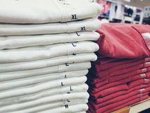 Stacked white and red t-shirts in shopping mall or department store royalty free stock photos