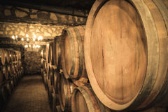 Stacked wine barrels in the old cellar of the winery. In underground winery stock photo