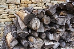 Stacked wood logs next to a rustic stone wall royalty free stock photos