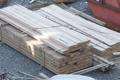 Stacked wooden boards at a construction site. Stock Photos