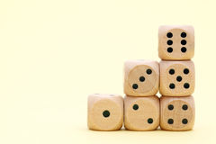 Stacked wooden dice. On a yellow background Stock Images