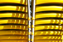 Stacked Yellow Chairs Close-up. Close-up on two rows of stacked yellow plastic chairs Stock Photo