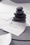 Stacked zen stones: business metaphor for balance. Metaphor of balance in business: stacked zen stone on papers/calendar Stock Photography