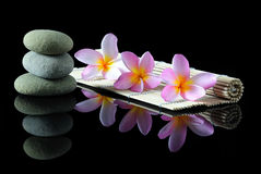 Stacked Zen stones Frangipani flowers. Spa, beauty and wellness concept - Stacked Zen stones Frangipani flowers on a bamboo mat with reflection, dark background stock image