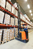 Stacker in modern big warehouse stock photography