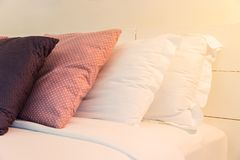 Stacking of blue backrest pillow and white pillow on bed and white brick wall. Interior modern bedroom Stock Image