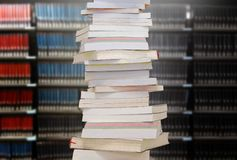Stacking books with blur bookshelfs background in library room. Stacking books with bookshelfs background in the library room. Education and knowledge high as a stock photo